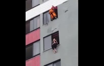 女跳樓坐窗邊 消防員將她踹進去   消防員在11樓準備垂降