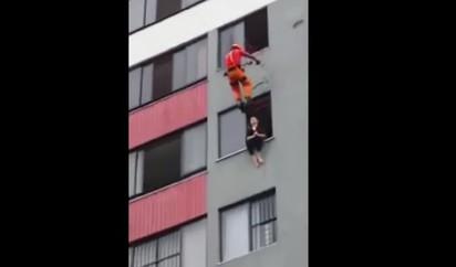 女跳樓坐窗邊 消防員將她踹進去   消防員垂降而下將女子踹進屋內
