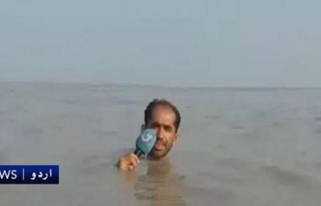 記者整個人浸到淹水中。(翻攝巴基斯坦《G TV》)