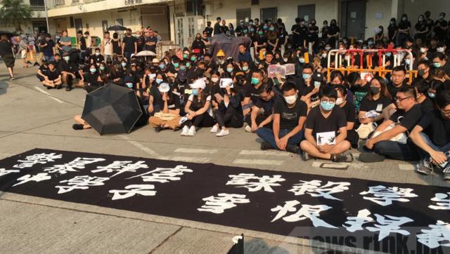 不滿警方開實彈,市民、校友在校外靜坐聲援中槍學生。(翻攝香港電台網站)