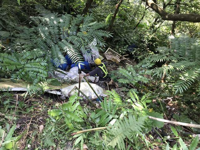 新北市環保局人員吊繩索深入山谷清除廢液桶