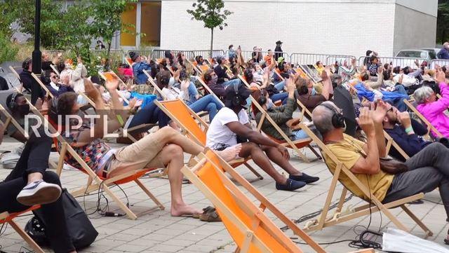 坐在輕便折疊躺椅上,放鬆地享受音樂。(翻攝自www.rt.com)