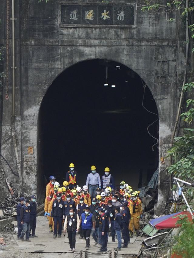 台鐵太魯閣號撞吊卡車嚴重出軌事件,搜救人員5日將 壓在第6節車廂下的罹難者救出,大批人員團團圍住遺 體走出隧道。(中央社)
