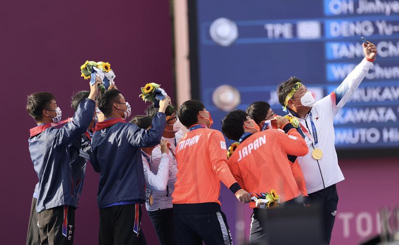 射箭男子團體賽,金銀銅牌分別由韓國(白衣)、台灣(藍衣)及日本(橘衣)拿下。頒獎典禮後,韓國隊提議3隊選手一起自拍留念。(中央社)