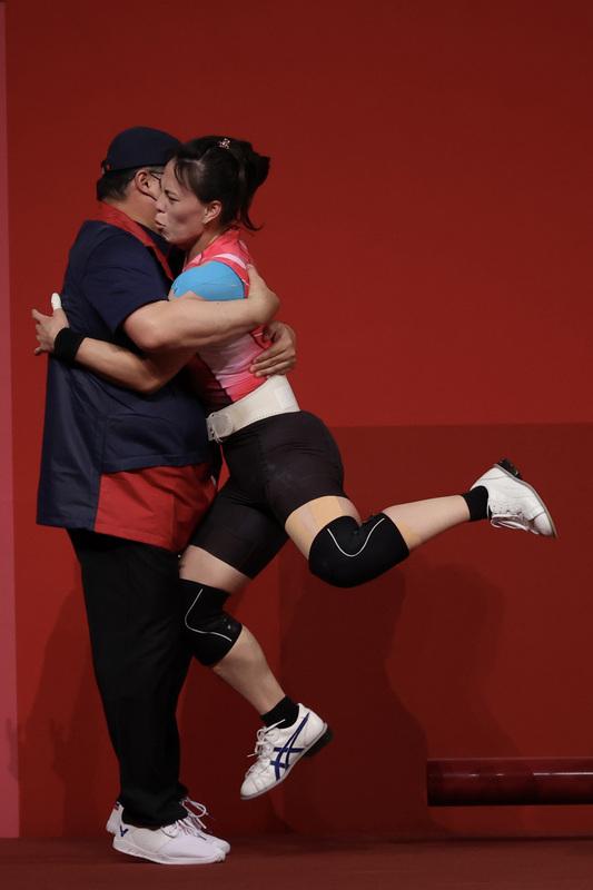 郭婞淳東奧舉重摘金,與教練相擁露出微妙表情。(中央社)